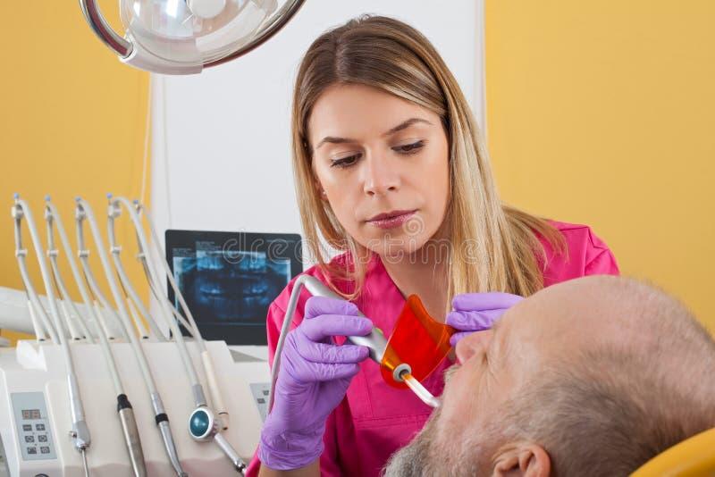 Polimerização dental no paciente idoso imagem de stock