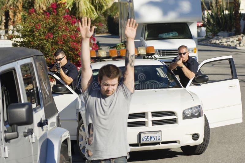 Polis Arresting Young Man royaltyfri bild