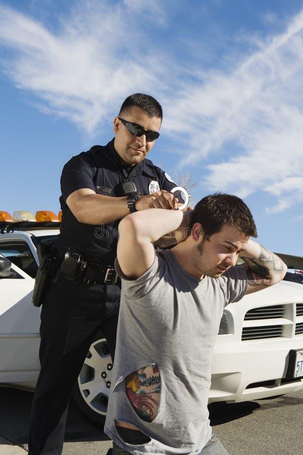 Polis Arresting Young Man royaltyfria bilder