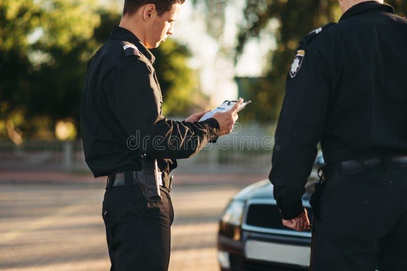 Polis en parada uniforme el coche en el camino fotografía de archivo