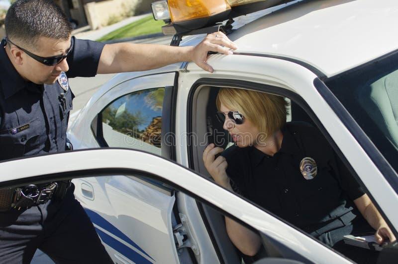 Polis Looking At Colleague royaltyfri bild