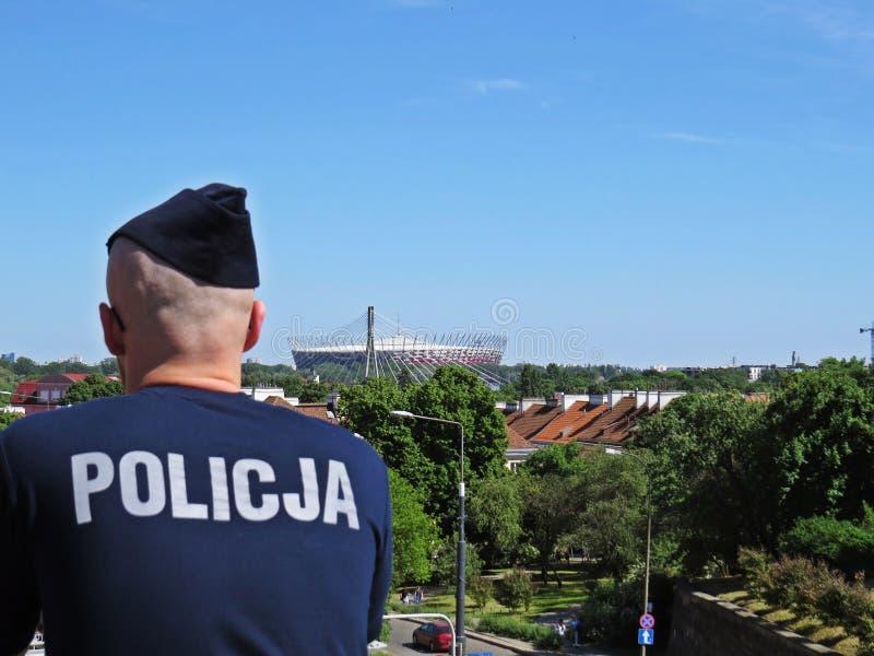 Polis med nationell fotbollsarena på bakgrund, Warszawa, Polen arkivfoton
