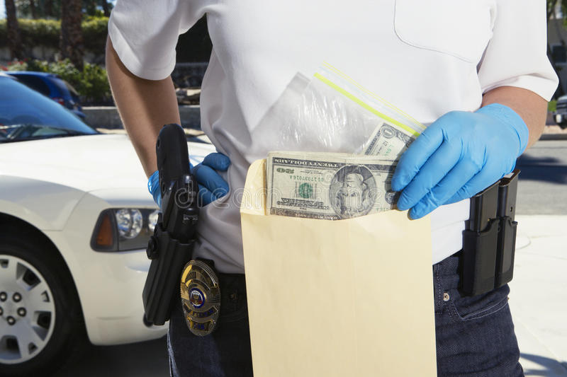 Polis Putting Money i teckenkuvert royaltyfri foto