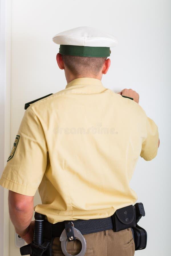Polis som knackar på ytterdörr arkivfoton