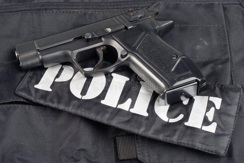 Polisbegreppshandeldvapen på svart enhetlig bakgrund arkivfoton