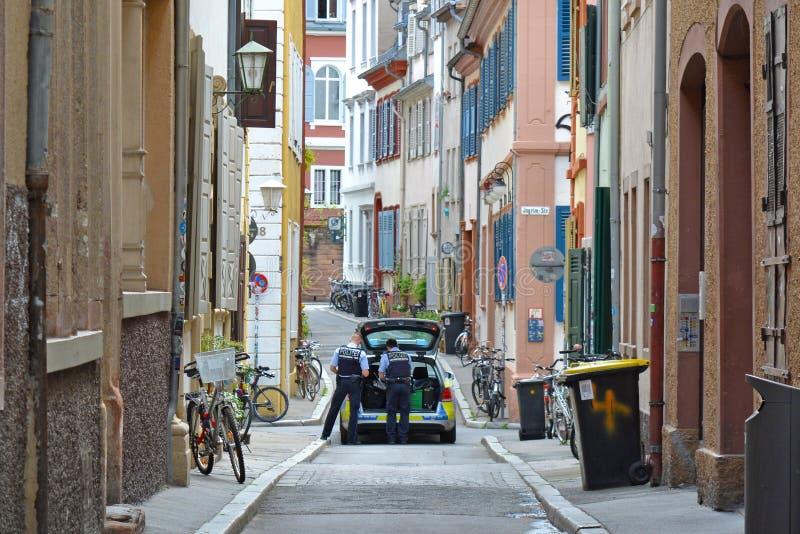 Polisbil med två tjänstemän på patrull i sidogata av det historiska centret fotografering för bildbyråer