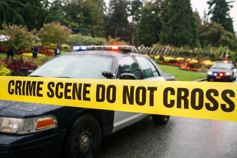 Polisbilar på brottsplatsen bak tejpad barriär royaltyfria foton