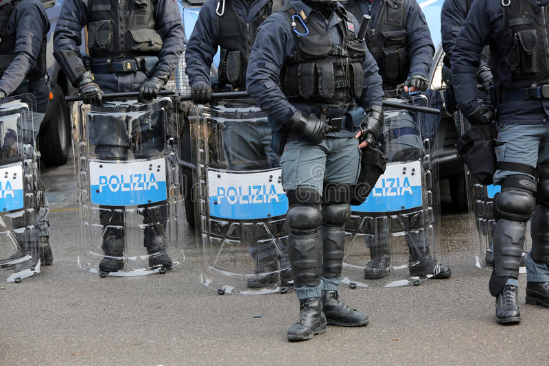 Polisen med sköldar och tumultkugghjulet under den sportsliga händelsen fotografering för bildbyråer