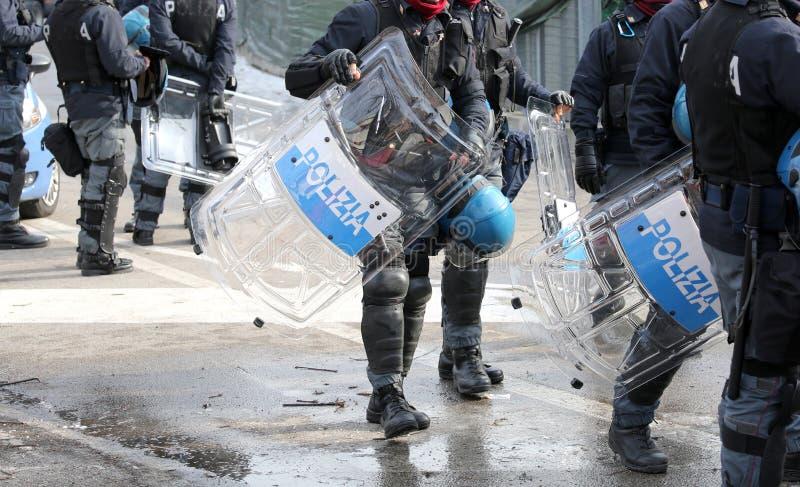 Polisen med sköldar och tumultkugghjulet under den sportsliga händelsen royaltyfria bilder