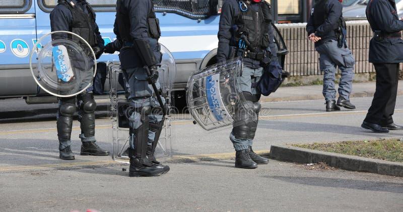 Polisen med sköldar och tumultkugghjulet under den sportsliga händelsen arkivfoton