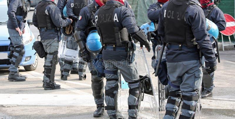 Polisen med sköldar och tumultkugghjulet under händelsen i staden royaltyfri fotografi
