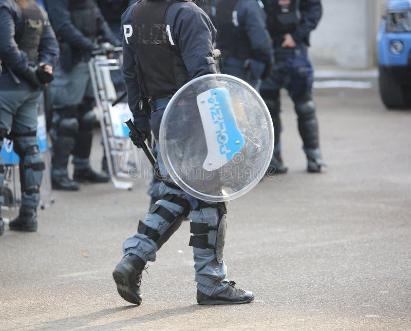 Polisen med sköldar och tumultkugghjulet under händelsen i staden arkivbilder