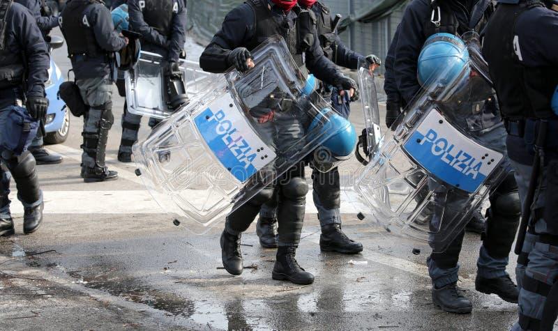 Polisen med sköldar och tumultkugghjulet under händelsen i staden arkivfoto