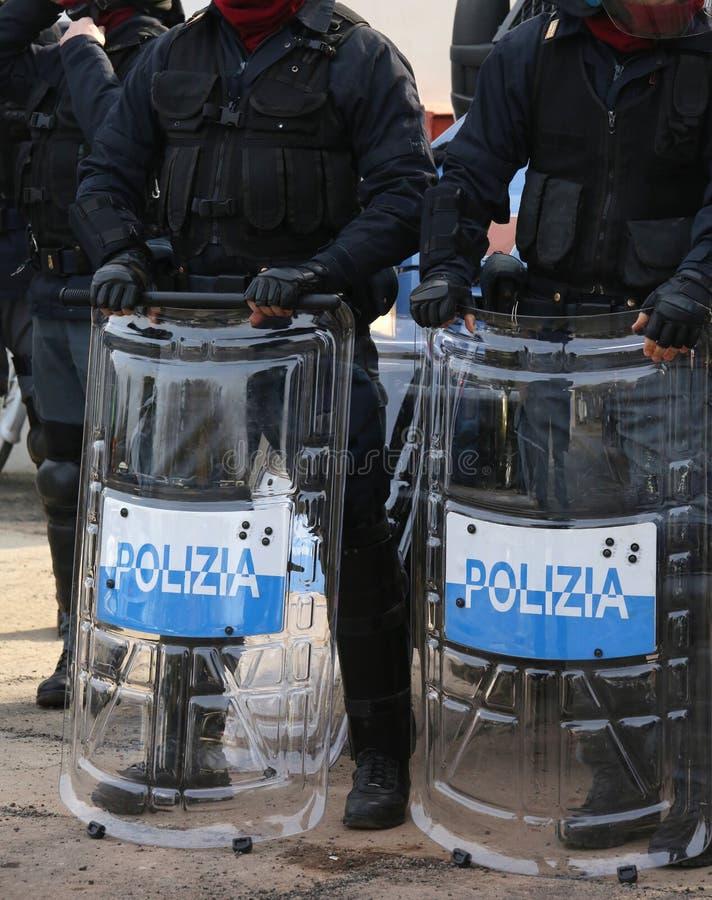 Polisen med sköldar och tumultkugghjulet under händelsen i staden arkivbild