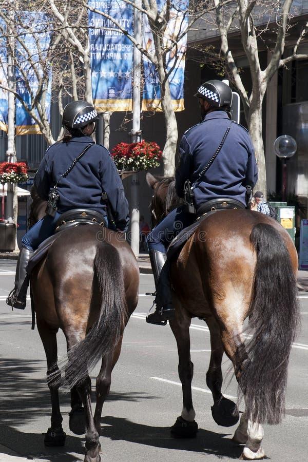 Polisen på hästar som patrullerar gatorna royaltyfri foto