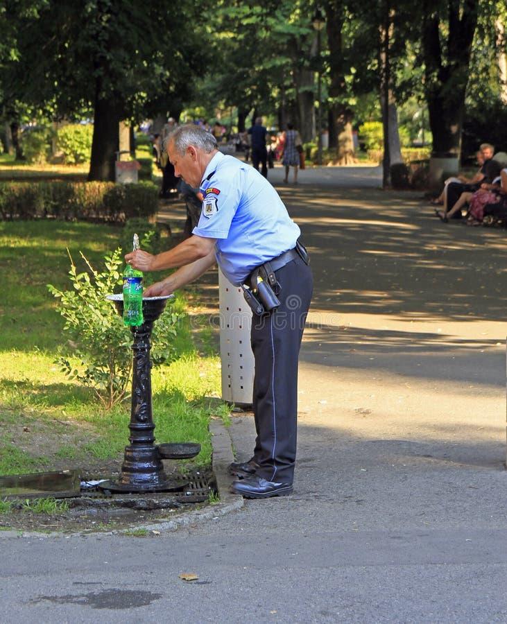 Polisen ska dricka vatten från gataspringbrunnen royaltyfri foto