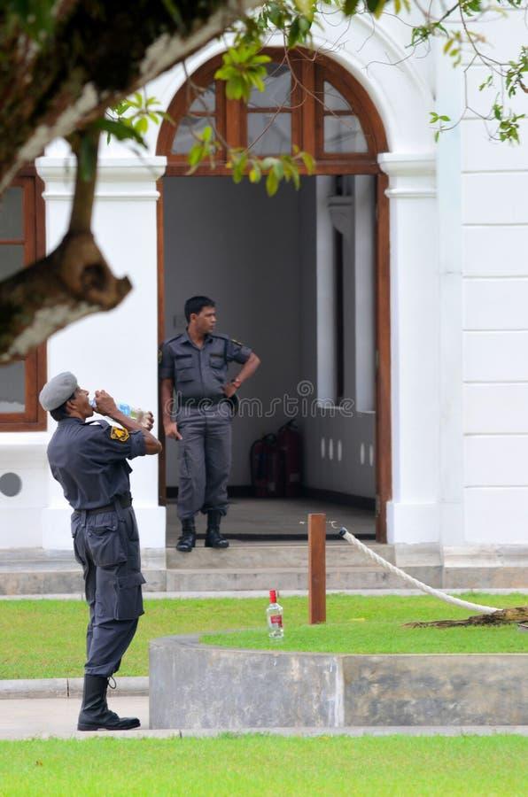 Poliser bevakar och dricker vatten på Arcade Independence Square Colombo Sri Lanka royaltyfria foton