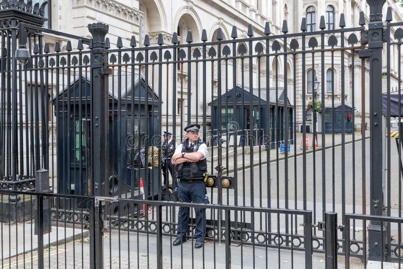 Poliser bevakar porten av Downing Street 10, London royaltyfri fotografi