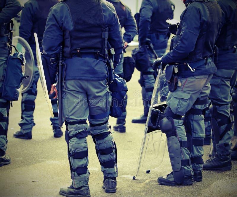 poliser i likformig under en tumult i staden med tappningeffe arkivfoton