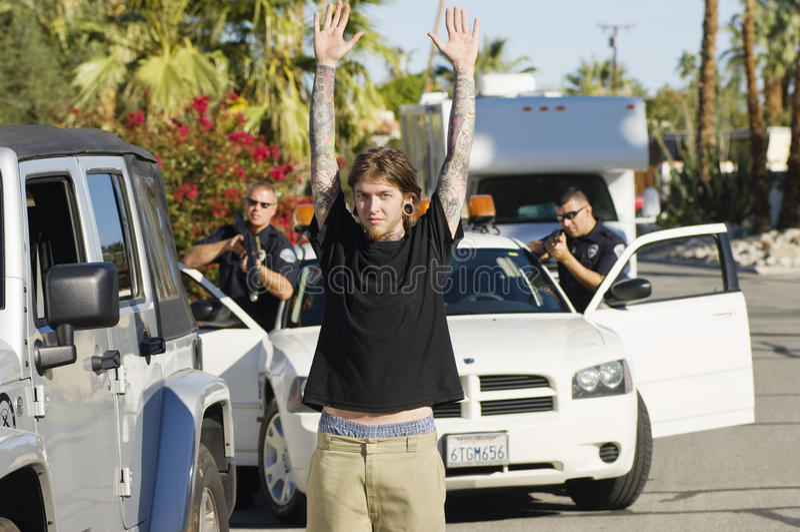 Poliser som arresterar den unga mannen arkivfoto