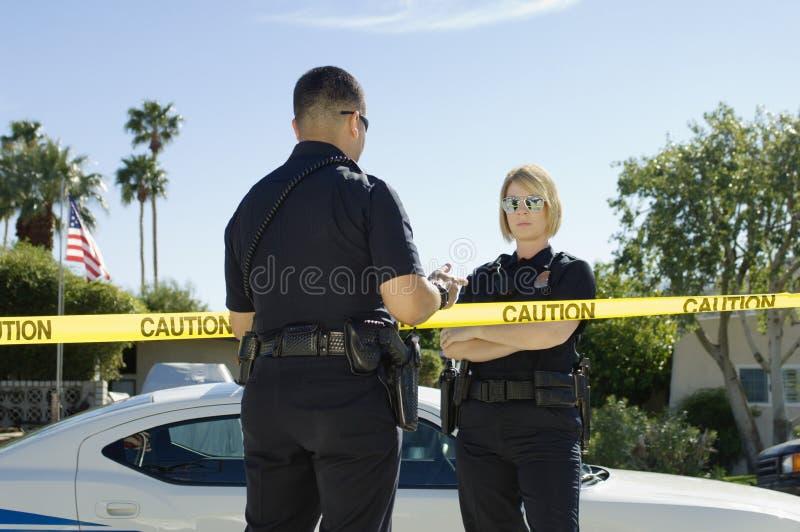 Poliser som avskiljs av varningsbandet arkivbilder