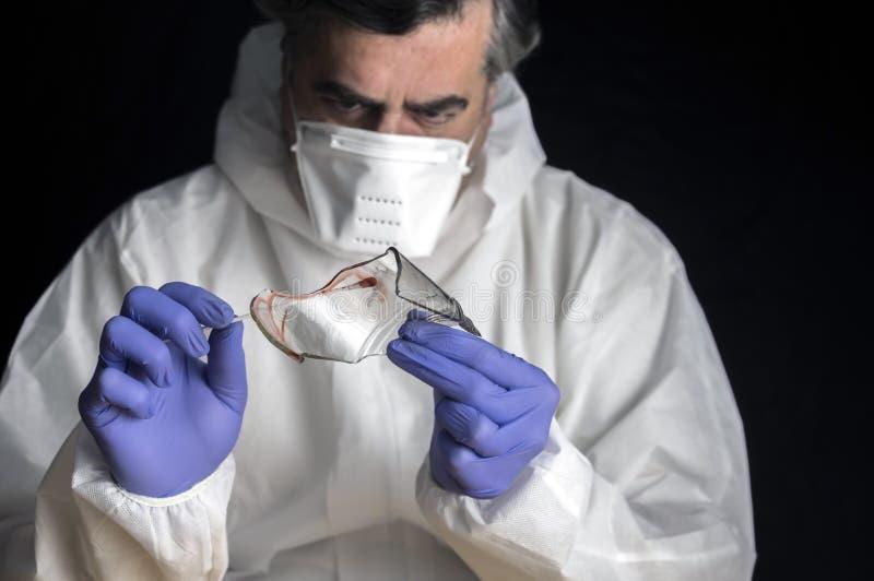 Polisexperten får blodprövkopian från en bruten glasflaska i criminalistic labb arkivfoto