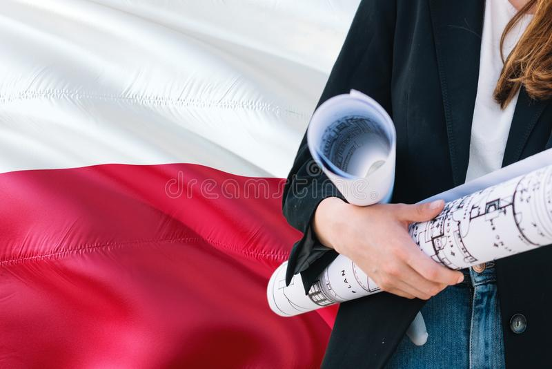 Polish Architect woman holding blueprint against Poland waving flag background. Construction and architecture concept.  royalty free stock photo