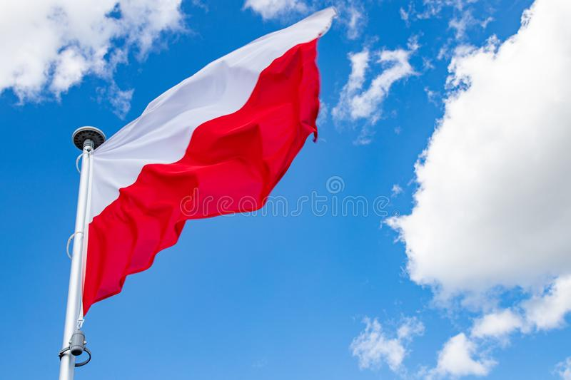 Polish flag on a background of the cloudy sky. National symbol of Poland on the mast royalty free stock photography