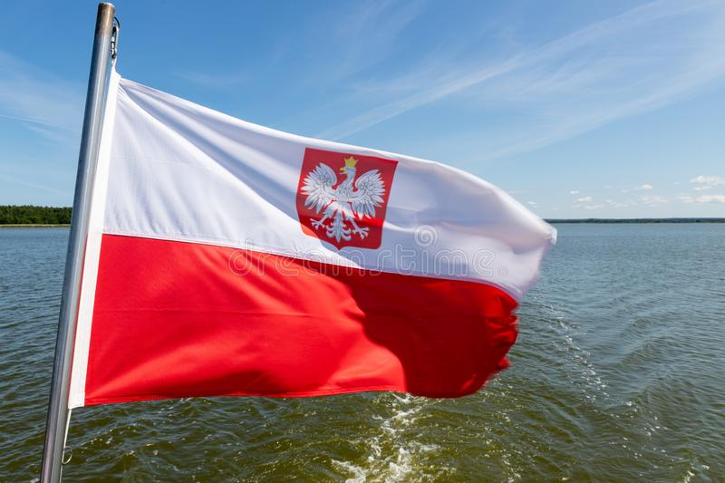 Polish flag suspended on the stern of a small inland ship. A vessel floating on a large lake in central Europe. Season of the summer, background, banner, blue royalty free stock photography