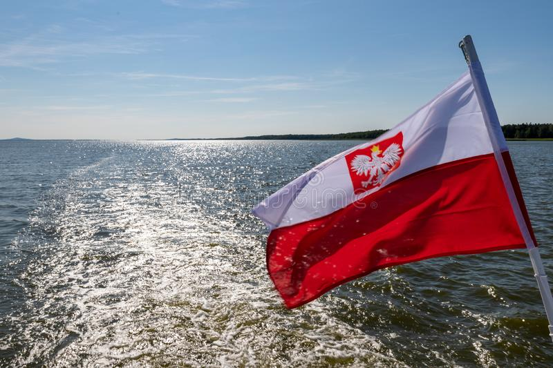 Polish flag suspended on the stern of a small inland ship. A vessel floating on a large lake in central Europe. Season of the summer, background, banner, blue stock image