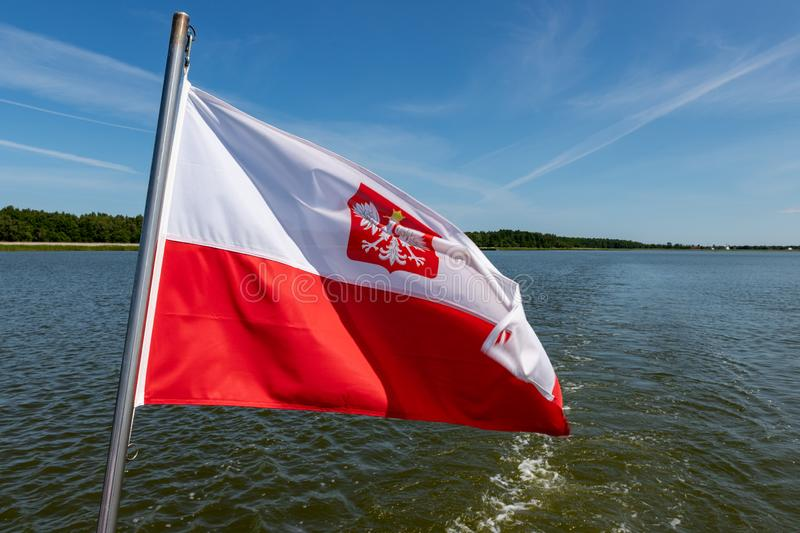 Polish flag suspended on the stern of a small inland ship. A vessel floating on a large lake in central Europe. Season of the summer, background, banner, blue royalty free stock image