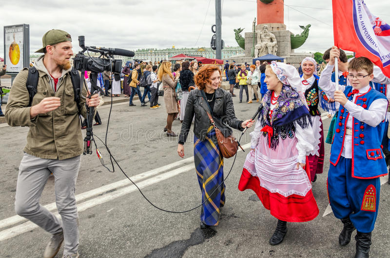 Polish folk dance ensemble GAIK are passing to the point of the performance. Giving interview on the go. Saint Petersburg, Russia, May 28, 2016. Ball of royalty free stock image