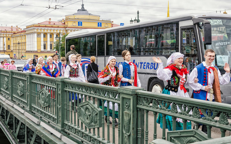 Polish folk dance ensemble GAIK are passing to the point of the performance over the Dvortsoviy bridge. Saint Petersburg, Russia, May 28, 2016. Ball of royalty free stock images