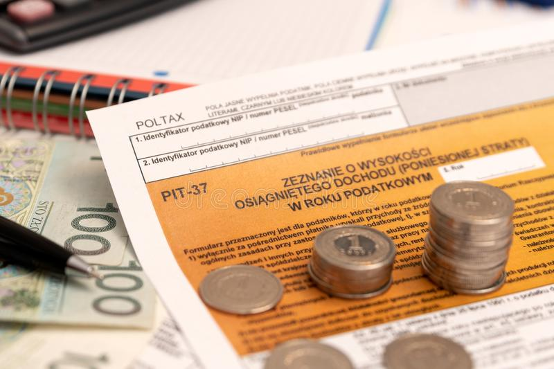 Polish individual income tax return concept. Polish individual income tax return. Stack of Polish coins on PIT-37 tax form royalty free stock photography