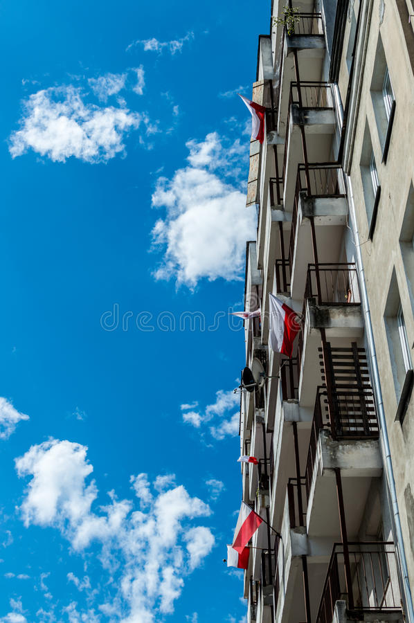 Polish national flags at block of flats during Independence Day and blue sky.  stock photography