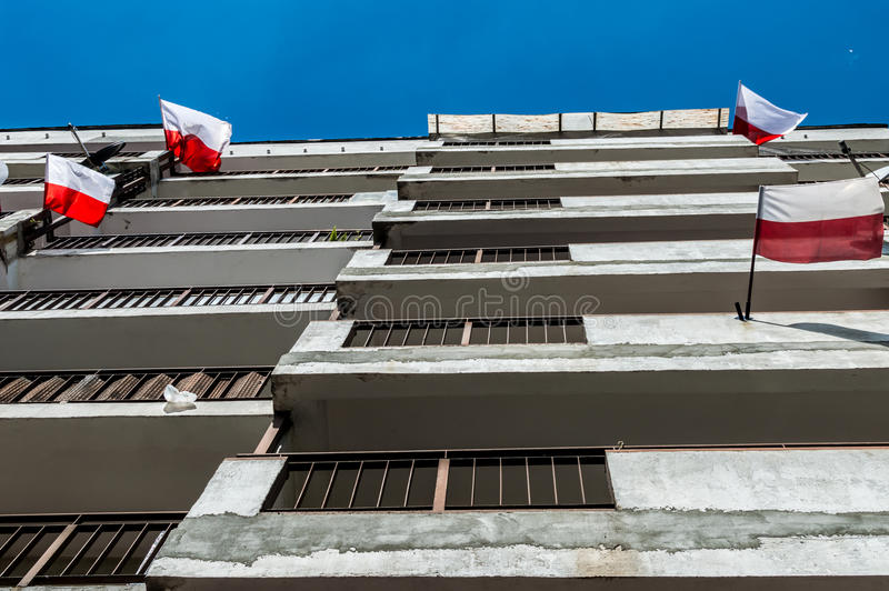 Polish national flags at block of flats during Independence Day and blue sky.  stock photos