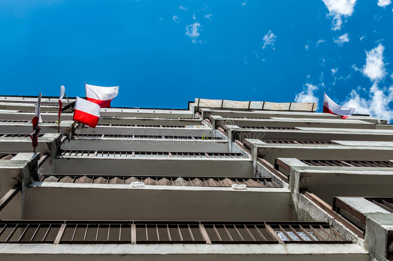 Polish national flags at block of flats during Independence Day and blue sky.  royalty free stock image