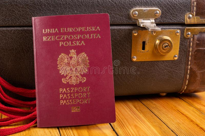 Polish passport and travel suitcase on a wooden table. Accessories for the traveler before the international trip. Bright background, abroad, airport, bag royalty free stock photos