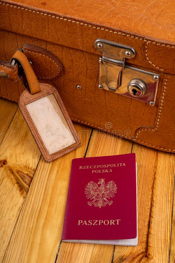 Polish passport and travel suitcase on a wooden table. Accessories for the traveler before the international trip. Bright background, abroad, airport, bag royalty free stock images