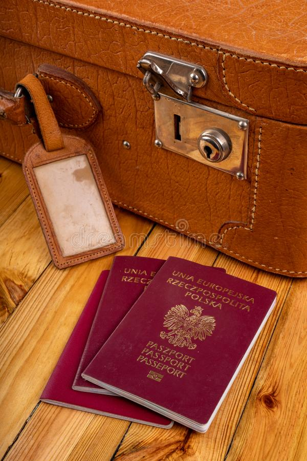 Polish passport and travel suitcase on a wooden table. Accessories for the traveler before the international trip. Bright background, abroad, airport, bag stock photography