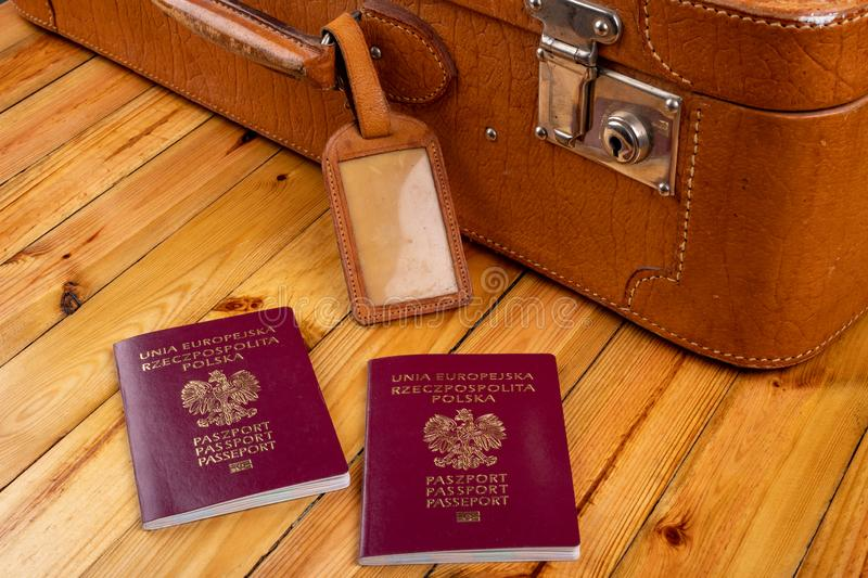 Polish passport and travel suitcase on a wooden table. Accessories for the traveler before the international trip. Bright background, abroad, airport, bag stock image