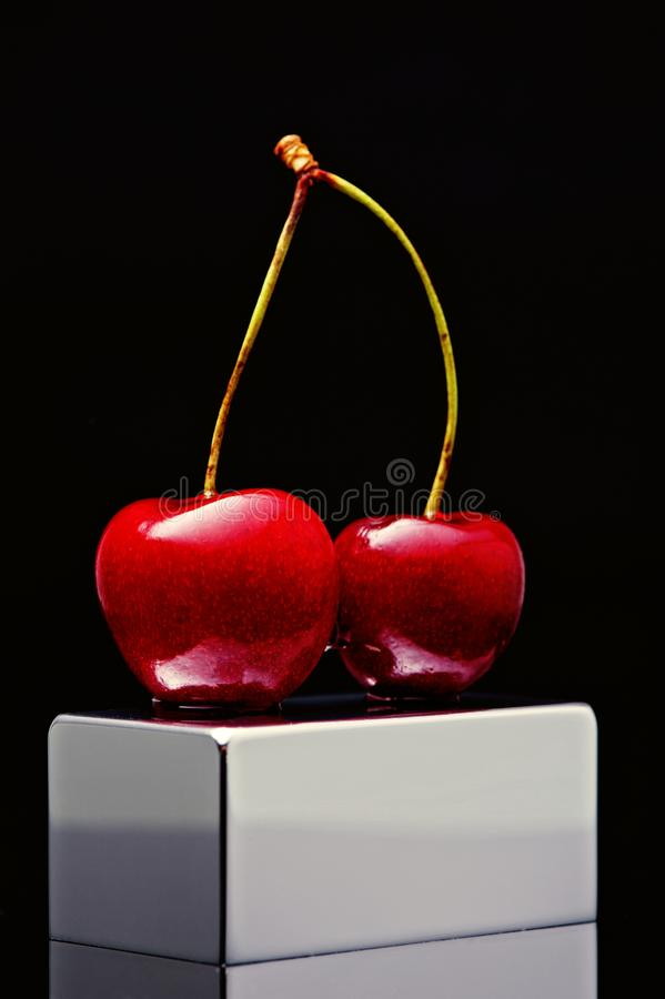Polish cherry on a chromed plinth on a black background royalty free stock photography