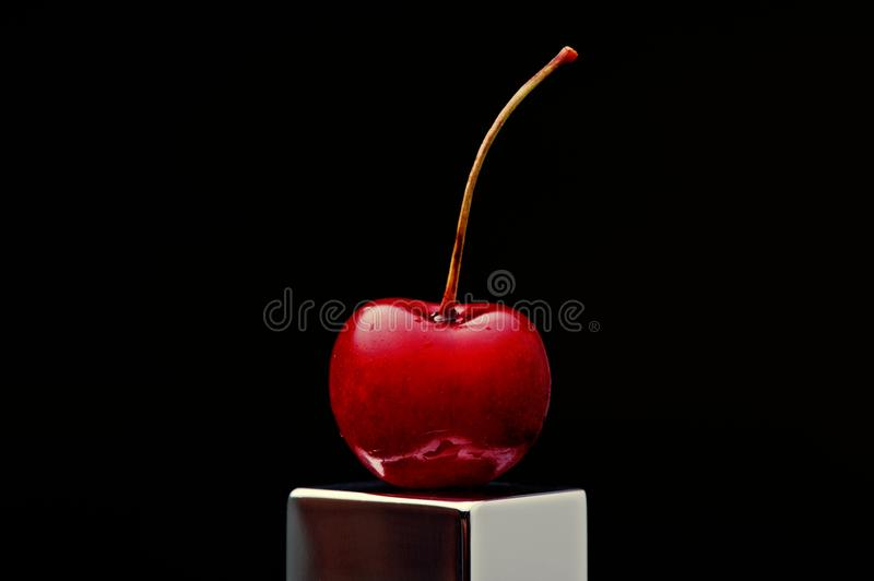 Polish cherry on a chromed plinth on a black background royalty free stock image