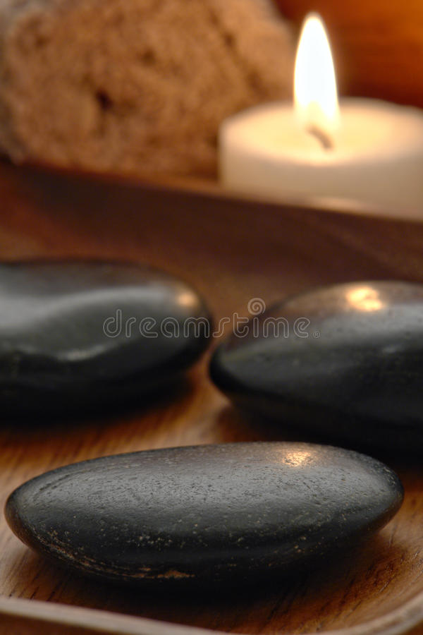 Polished Hot Massage Stones and Candle in a Spa royalty free stock photo