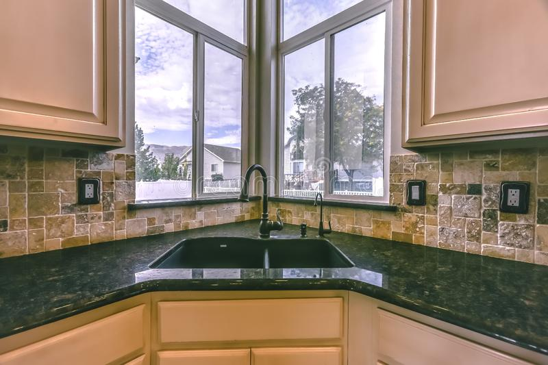 Polished kitchen interior of home with scenic view. Kitchen interior of a home with polished green countertop and sink. The corner window has a scenic view of royalty free stock photos