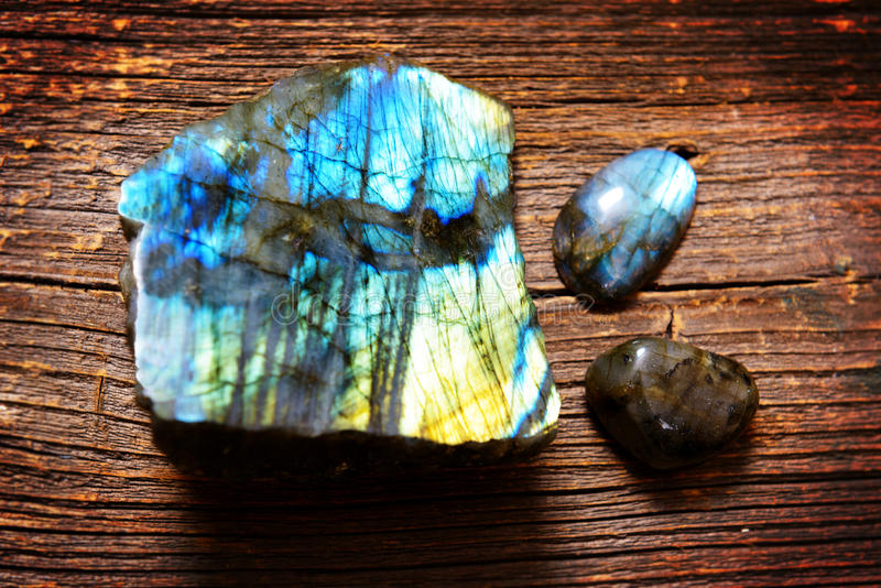 Polished labradorite crystals. On wooden board stock images