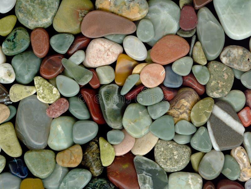 Polished Rocks. Polished pebbles and semi-precious stones background royalty free stock photos