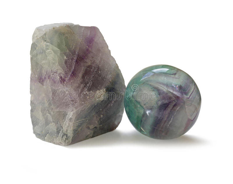 Polished and rough natural specimens of Fluorite banded crystal. Two different specimens of fluorite, one chunk unpolished and one shaped and polished on white stock photo