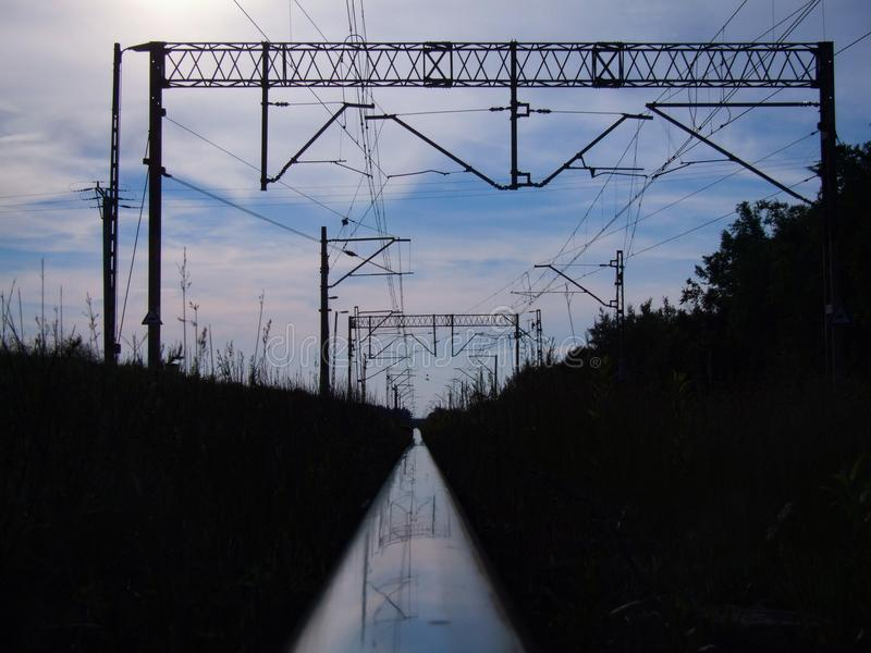 Rail track reflecting blue sky and railroad infrastructure stock photography