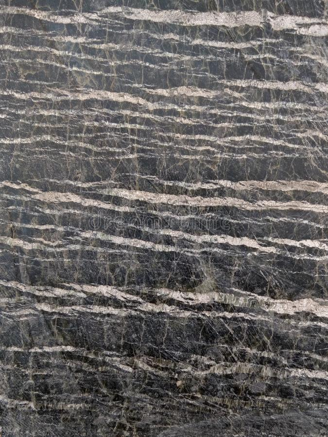 Polished stone serpentine with streaks of asbestos chrysotile. Dark gray with light stripes royalty free stock photos